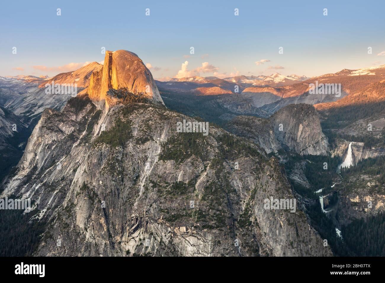 El pico Half Dome y la cascada Yosemite Falls como se ve Desde Glacier Point al atardecer Foto de stock