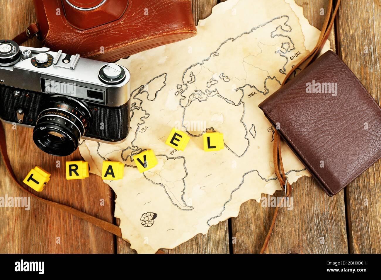 Cámara retro en mapa del mundo con palabra Viajes sobre fondo de mesa de madera Foto de stock