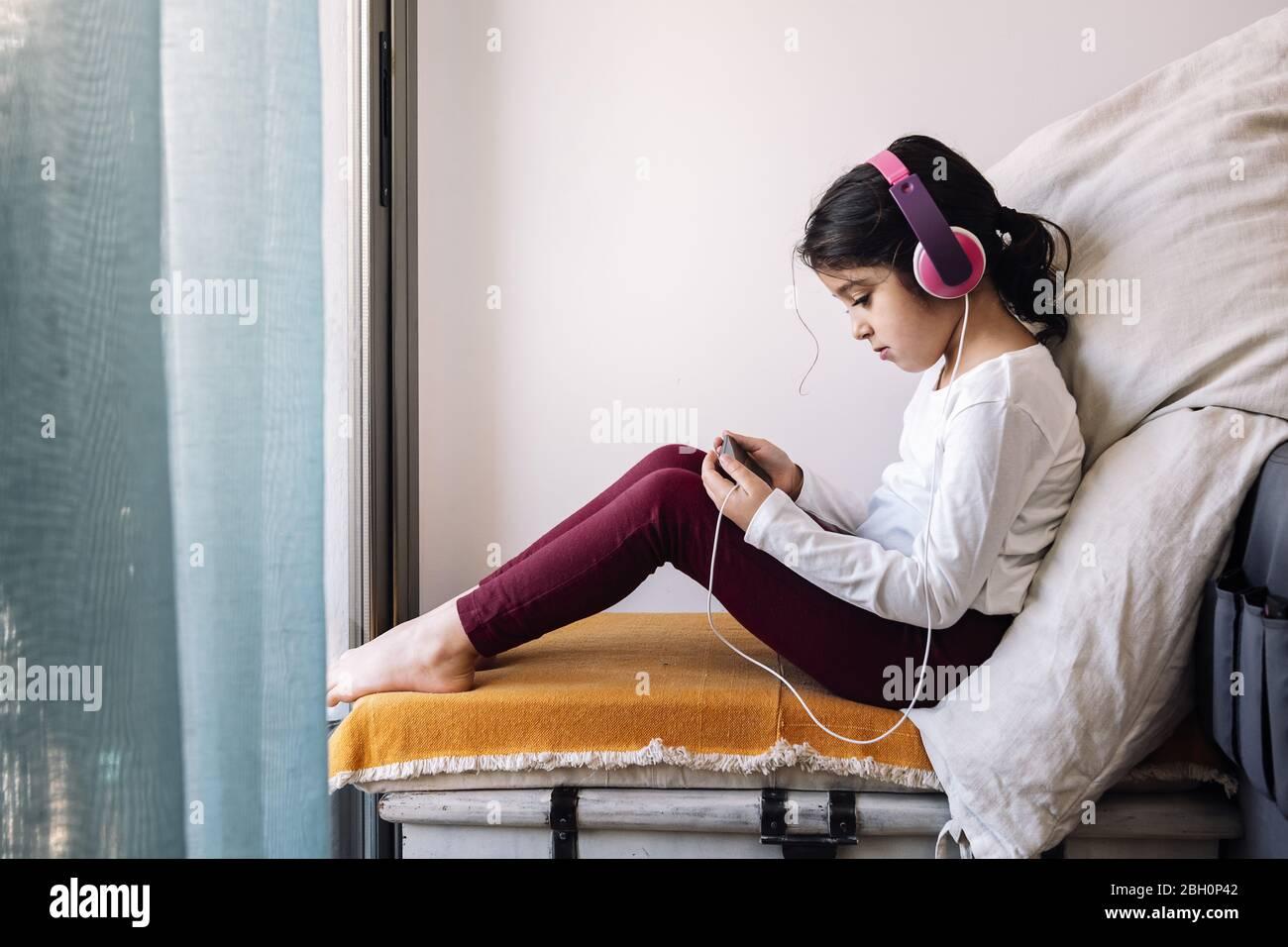 niña sentada frente a su ventana con auriculares viendo vídeos en el teléfono, entretenimiento en casa para niños concepto Foto de stock