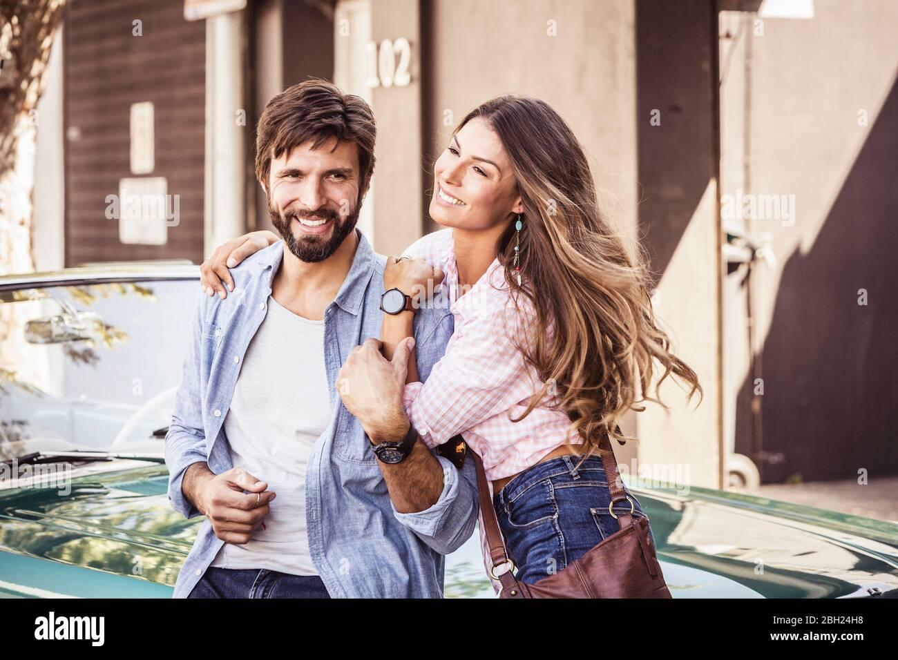 Feliz pareja en un coche convertible fuera de casa Foto de stock