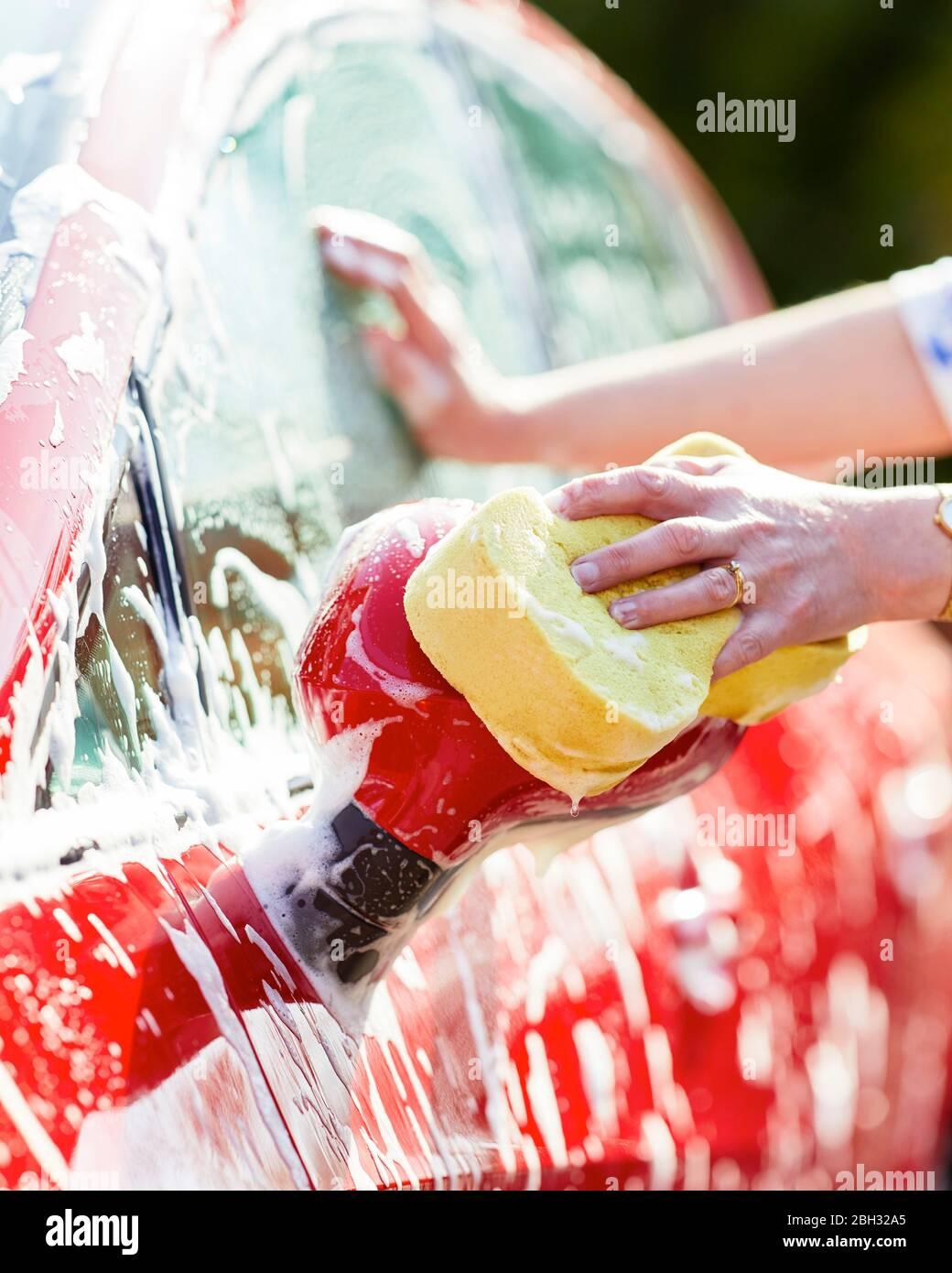 Mujer lava su automóvil Foto de stock