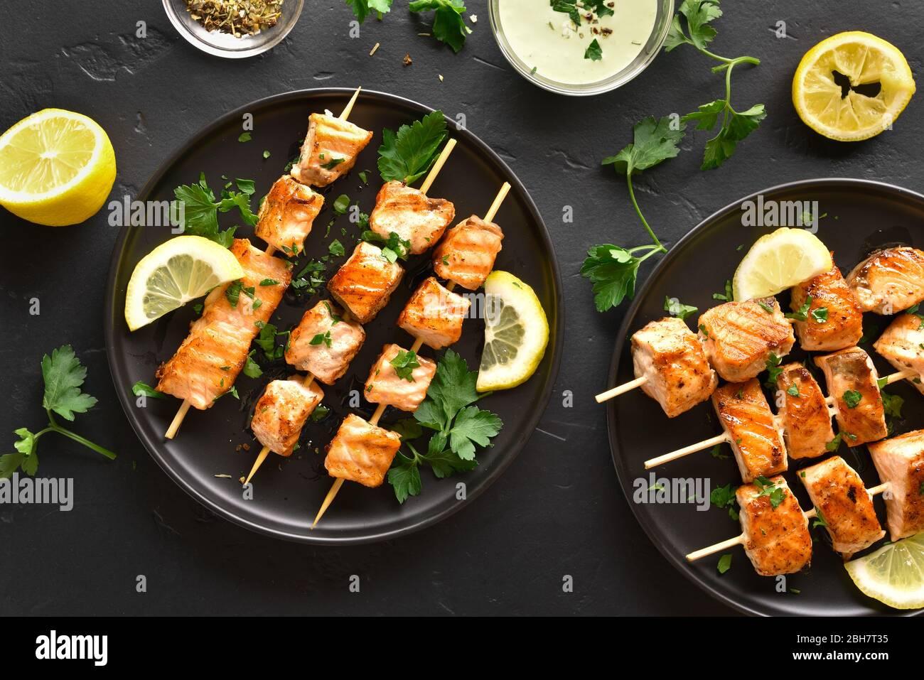 Salmón grillado kebab. Barbacoa pinchos de salmón sobre fondo de piedra negra. Vista superior, laicos plana Foto de stock