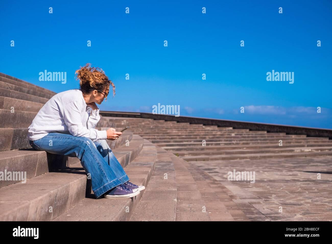 bonita chica swirl cabello marrón sentarse en un hermoso lugar urbano con el cielo panorama utilizando la tecnología móvil para mantenerse conectado con amigos y personas por todas partes. moderno no solo concepto Foto de stock