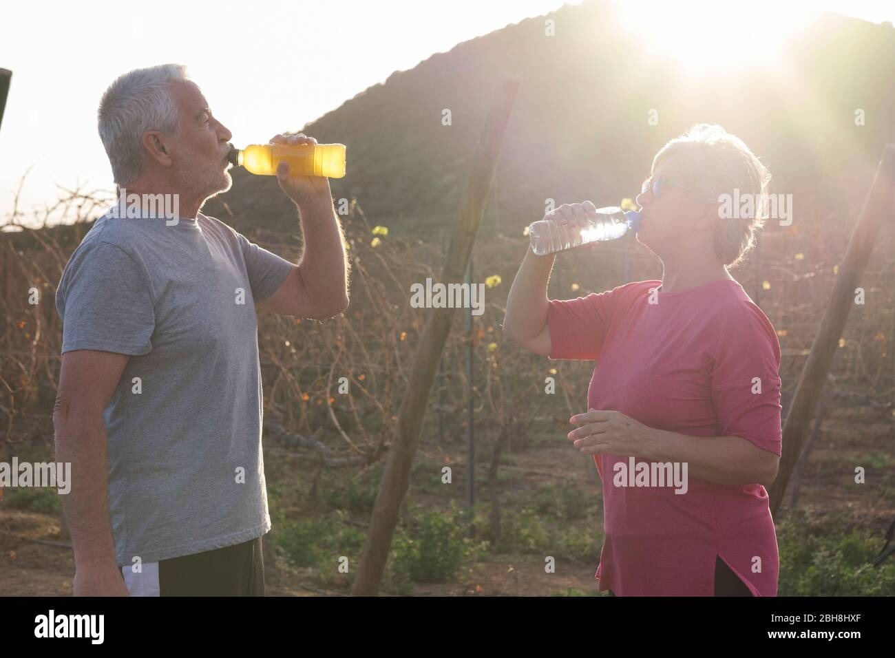 Un par deportivo de personas mayores caucásicas beber agua y beber energía después de correr en el campo al aire libre para un estilo de vida saludable jubilados concepto Foto de stock