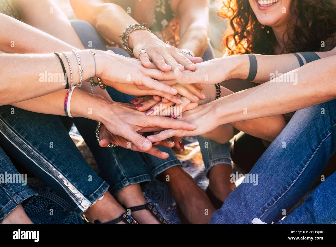 Felicidad y estilo de vida alegre para las chicas del concepto de equipo poniendo las manos juntas para siempre amigos - felicidad y amistad grupo de mujeres sonríe y se divierten con el sol en la retroiluminación Foto de stock
