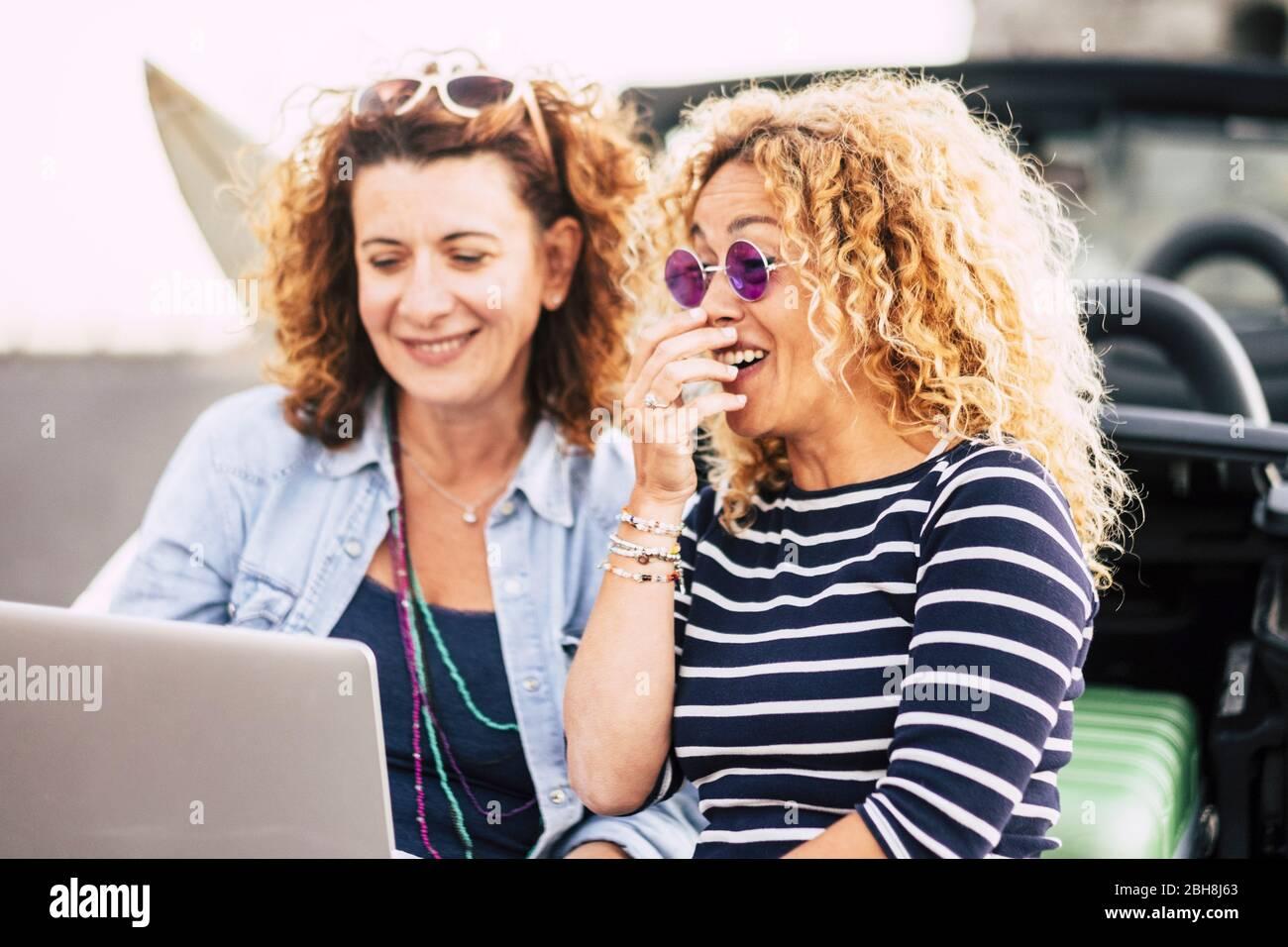 Un par de mujeres jóvenes rizado y hermosas se divierten riendo con un portátil al aire libre - concepto de gente y tecnogia - cosas divertidas para las mujeres bonitas - estilo de vida de risa y sonrisa Foto de stock