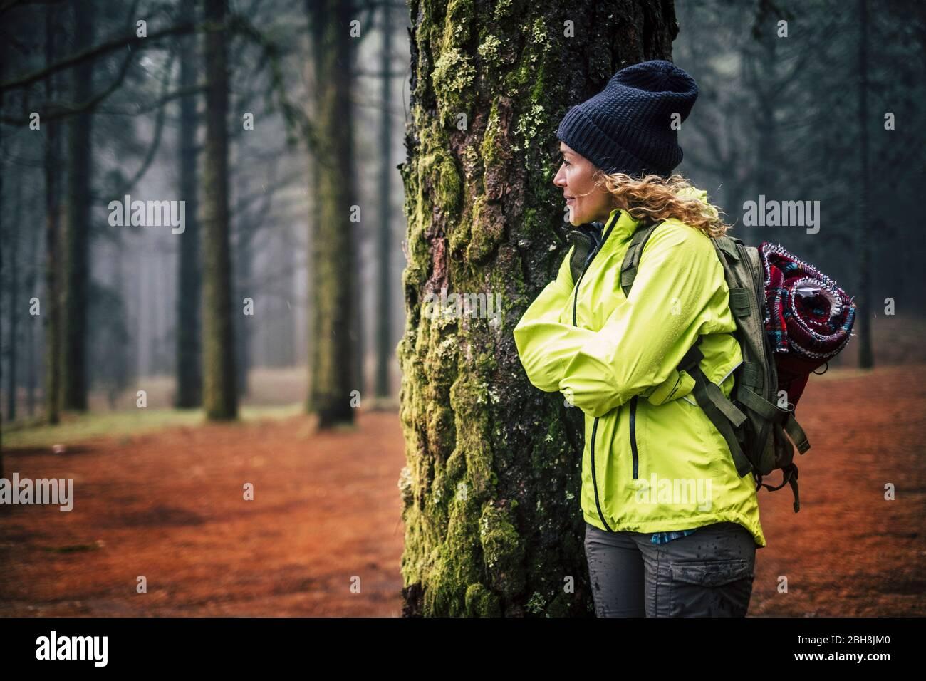 Mujer de edad media caucásica solitaria de pie en el bosque y mirar la hermosa madera a su alrededor - concepto de vacaciones de senderismo alternativo en el salvaje al aire libre - mochilero y la gente de viaje Foto de stock