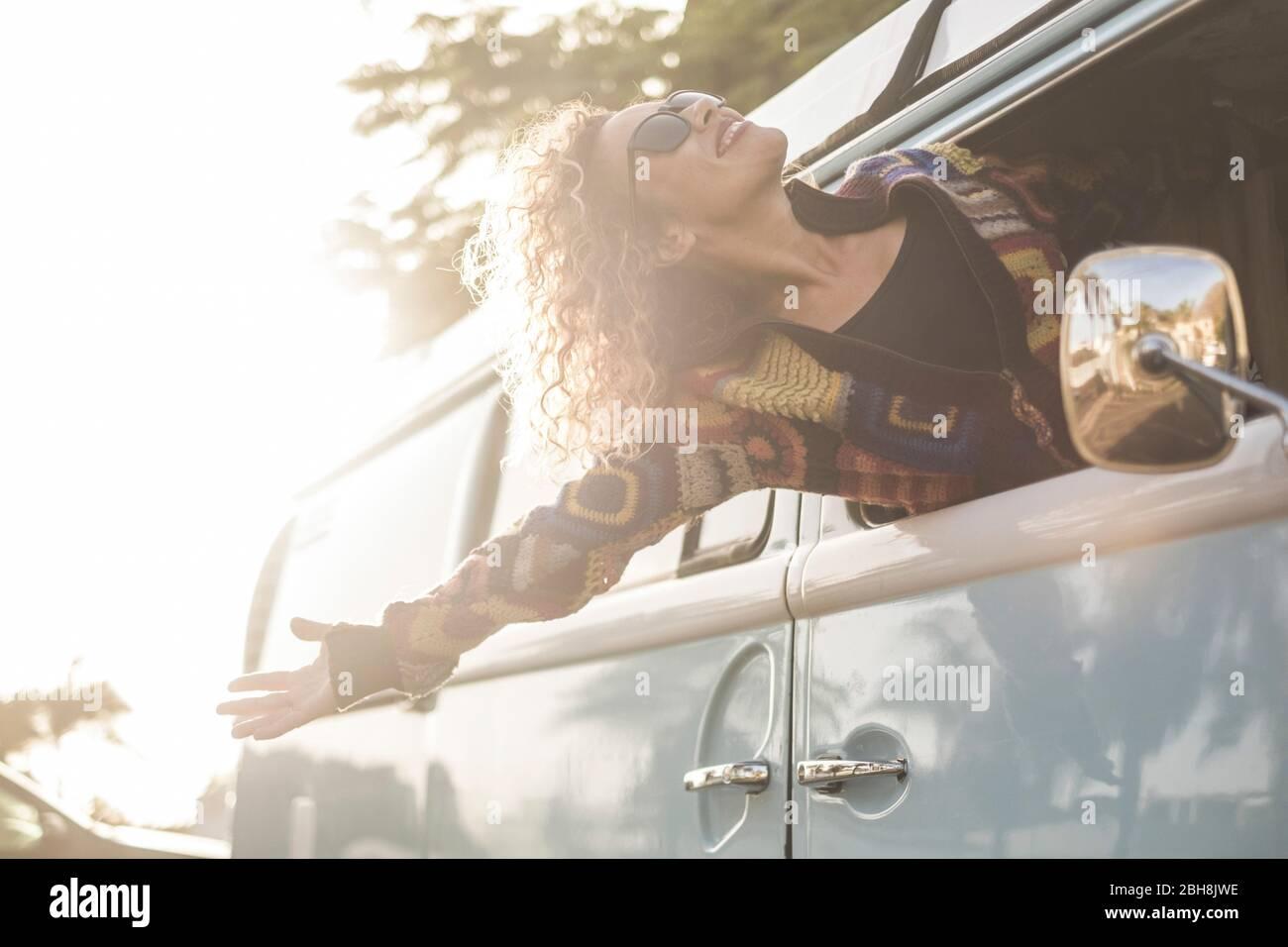 Felicidad y libertad concepto de estilo de vida con hermosa niña joven caucásica mujer fuera del vehículo disfrutando del viento y sentir el aire libre - viaje y vacaciones concepto de transporte para la moda chica Foto de stock