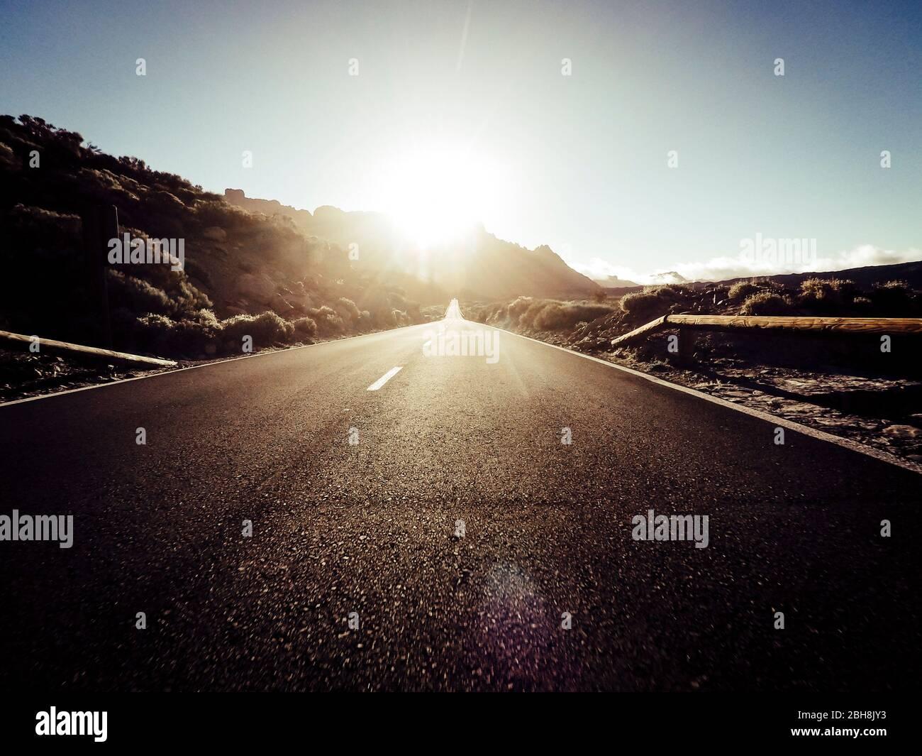 Camino largo en la montaña con sol en frente y efecto de luz solar - punto de vista del suelo con asfalto negro y líneas blancas - conducción y concepto de viaje Foto de stock
