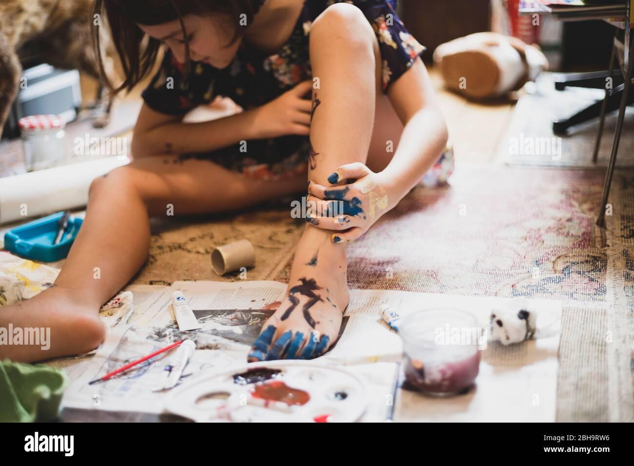 Niña jugando en casa y pintando su pie y mano. Foto de stock