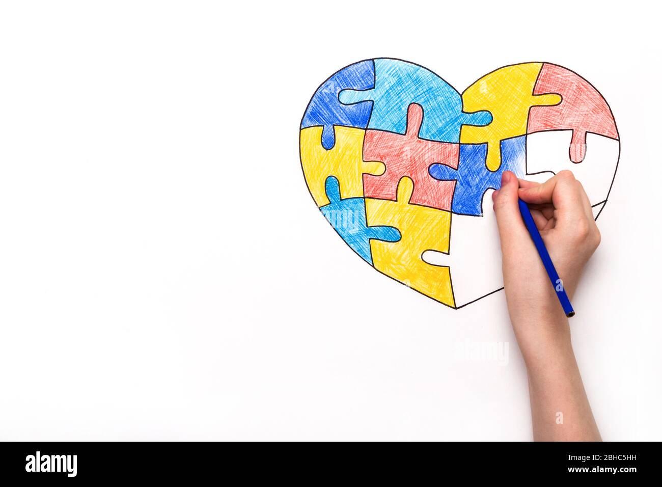 Día Mundial de la conciencia del Autismo. La mano de los niños dibuja el corazón de rompecabezas multicolor. Concepto de atención de salud mental. Foto de stock