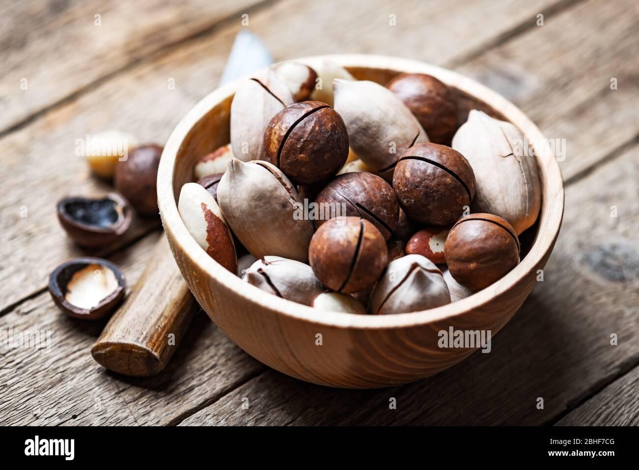 Nueces mixtas secas en un cuenco de madera de primer plano. Nueces de macadamia, pacán y Brasil con cuchillo sobre mesa de madera. Disparo macro de estudio. Foto de stock