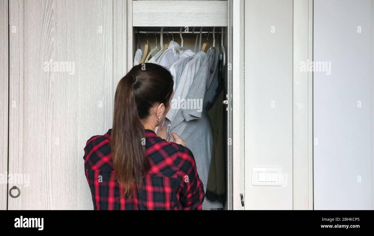 Una Señora De Pelo Largo Con Cola De Caballo Clasifica La Ropa Blanca En El Armario Mirando A Diferentes Perchas Cerca De La Parte Trasera Fotografía De Stock Alamy