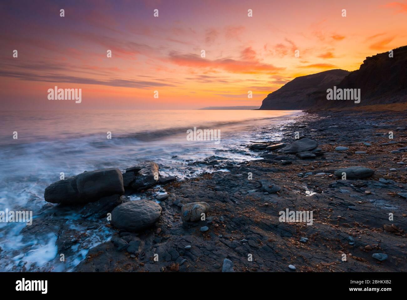 Seatown, Dorset, Reino Unido. 26 de abril de 2020. Clima en Reino Unido. Las nubes brillan de naranja al atardecer en Seatown en Dorset mirando hacia el oeste hacia los acantilados de Golden Cap. Crédito de la imagen: Graham Hunt/Alamy Live News Foto de stock