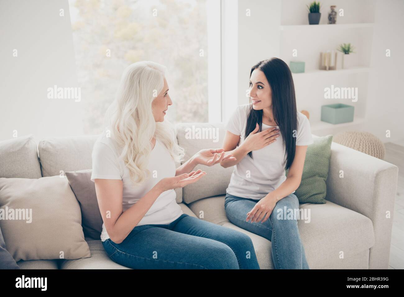 Retrato de dos mujeres agradables, alegres y agradables hablando de noticias compartiendo secretos pasando el día juntos en el interior de luz blanca Foto de stock