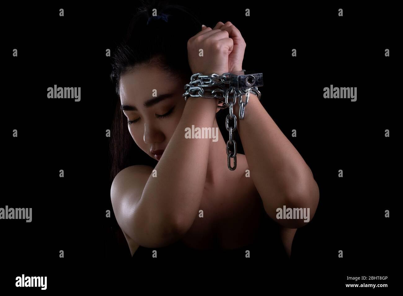 Retrato de una joven mano atada con cadena de acero y candado en el fondo negro, violaciones de los derechos humanos y el concepto del día Internacional de la Mujer, Fr Foto de stock