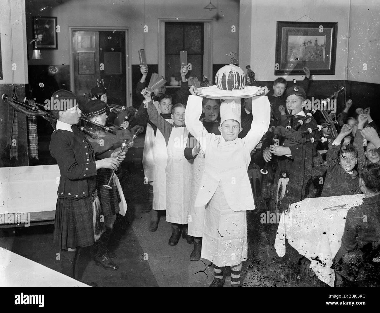 Las celebraciones navideñas ya han comenzado en una casa de Barnardo . - las fiestas navideñas han hecho un comienzo temprano en Dalziel del Dr. Barnardo de Wooler Memorial Home , Kingston , donde los puddings de Navidad fueron enlatados con una ceremonia elaborada . - Shows de fotos , chicos que animan como un pudín de Navidad llegan en plena regalia . - 30 de noviembre de 1935 Foto de stock
