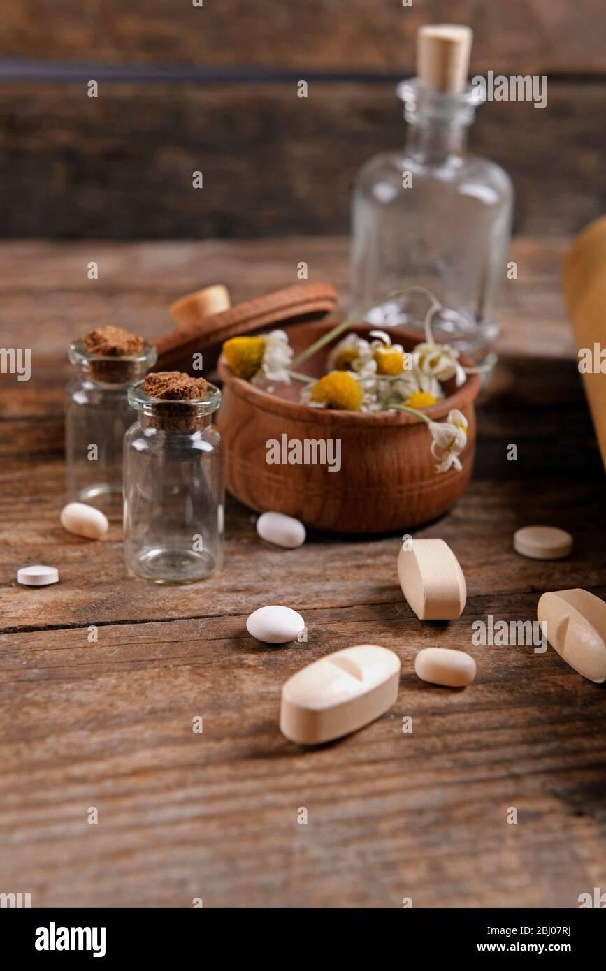 Secar las flores en mortero con las tabletas en la mesa de cerca Foto de stock