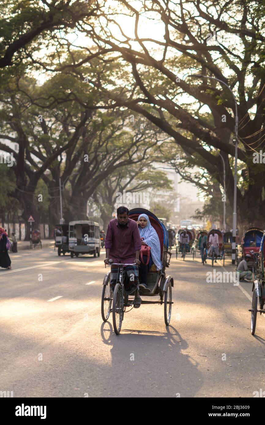 Dhaka / Bangladesh - 14 de enero de 2019: Rickshaw transportando pasajeros en una hermosa calle rodeada de árboles verdes Foto de stock