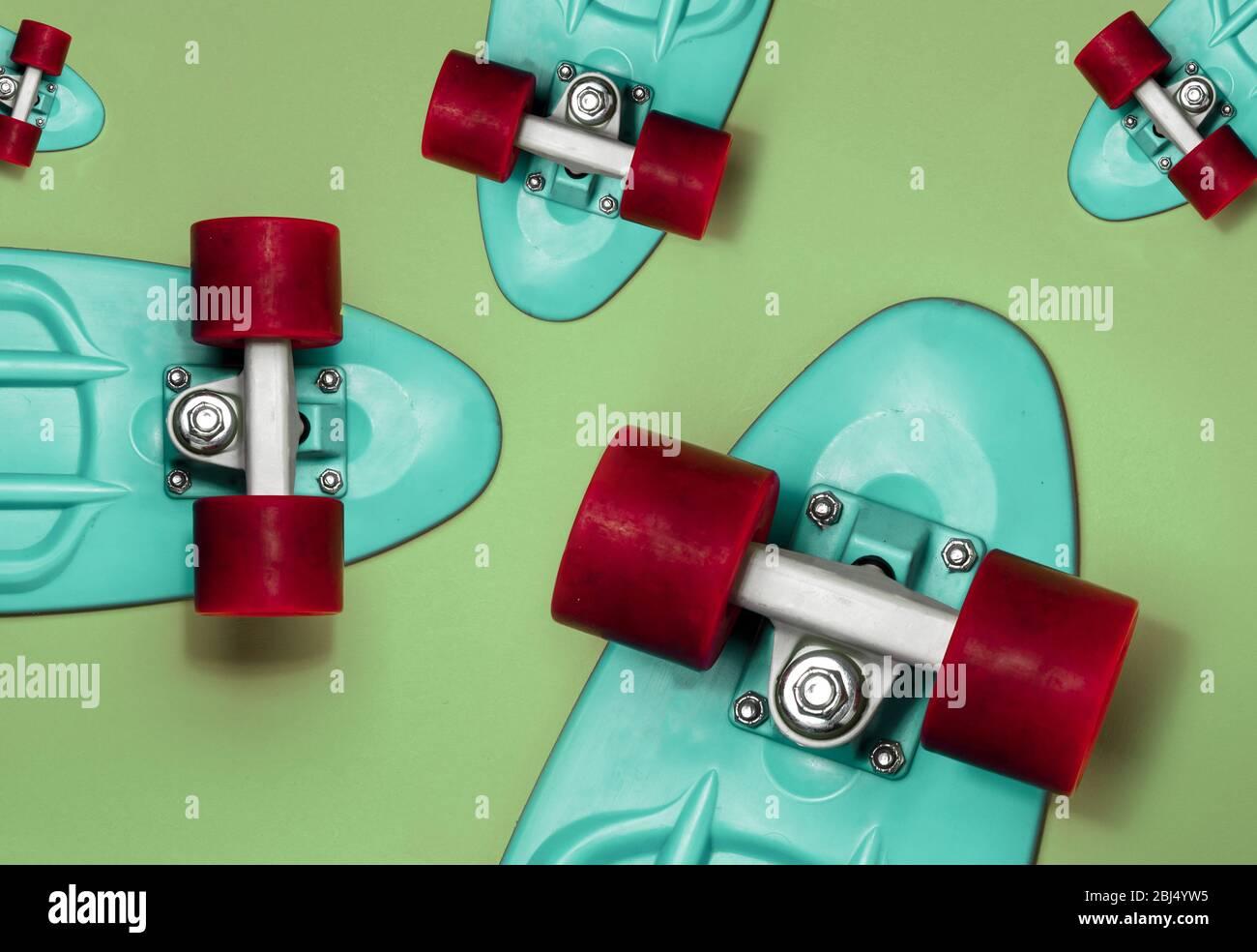 Turquesa Skateboards sobre fondo verde, vista superior. Concepto de estilo de vida deportivo, cultura, ocio, hobby, transporte alternativo Foto de stock