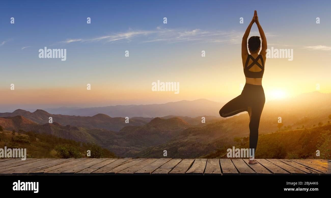 Mujer joven practicando yoga en la felicidad de la naturaleza.mujer. Pose equilibrio cuerpo vital zen y meditación para entrenar naturaleza montaña fondo en morni Foto de stock