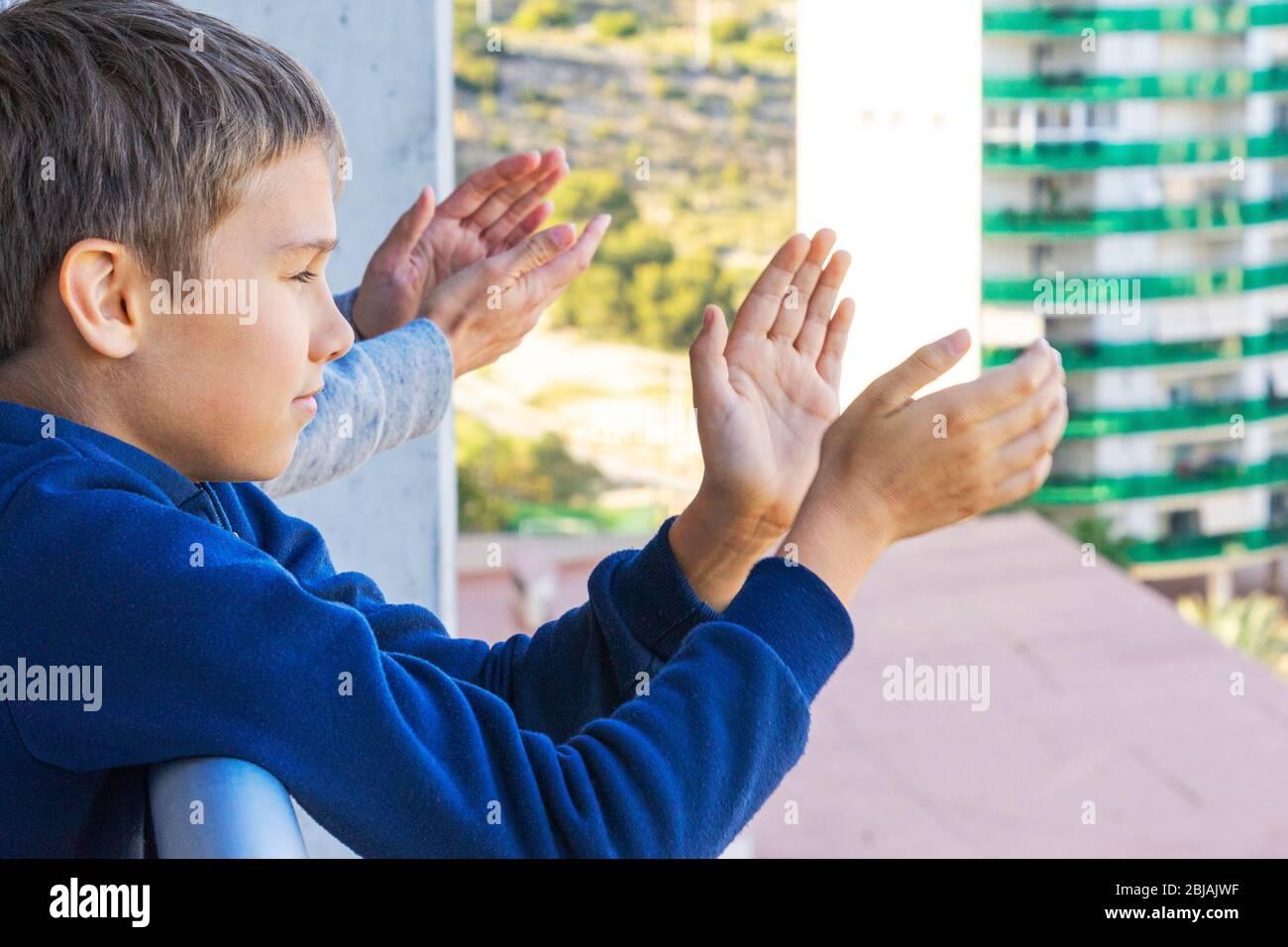 Familia aplaudiendo al personal médico desde el balcón. Las personas golpean los balcones y las ventanas para apoyar a los trabajadores de la salud durante la pandemia del Coronavirus Foto de stock