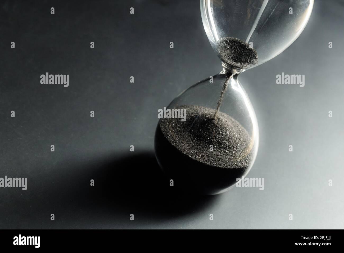 Reloj de arena sobre fondo oscuro. Foto macro. Primer plano. Foto de stock