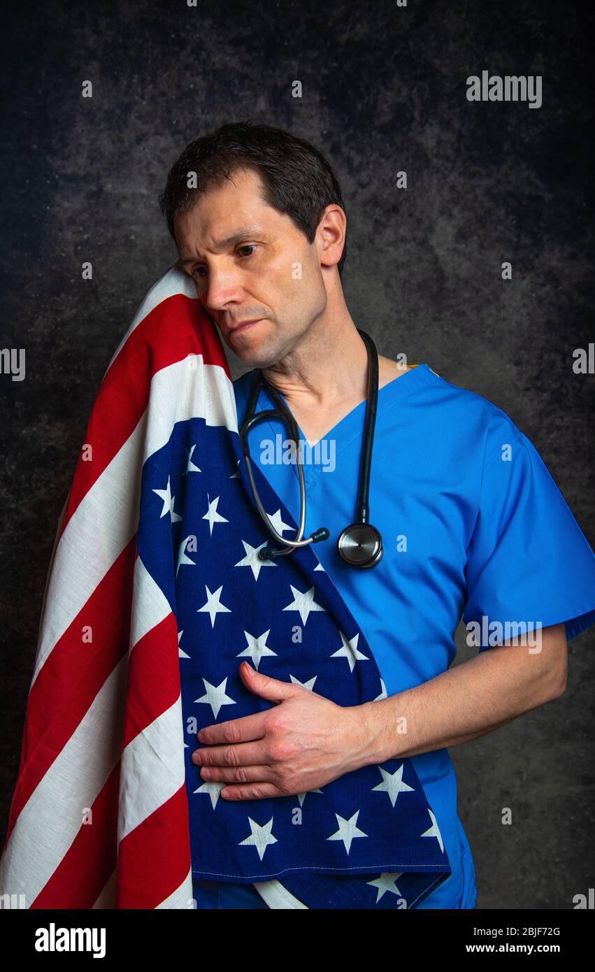 El médico triste/pensivo masculino en el hospital azul frota con estetoscopio, amamantando la bandera americana de Stars & Stripes cerca de su pecho, contra un estudio oscuro. Foto de stock