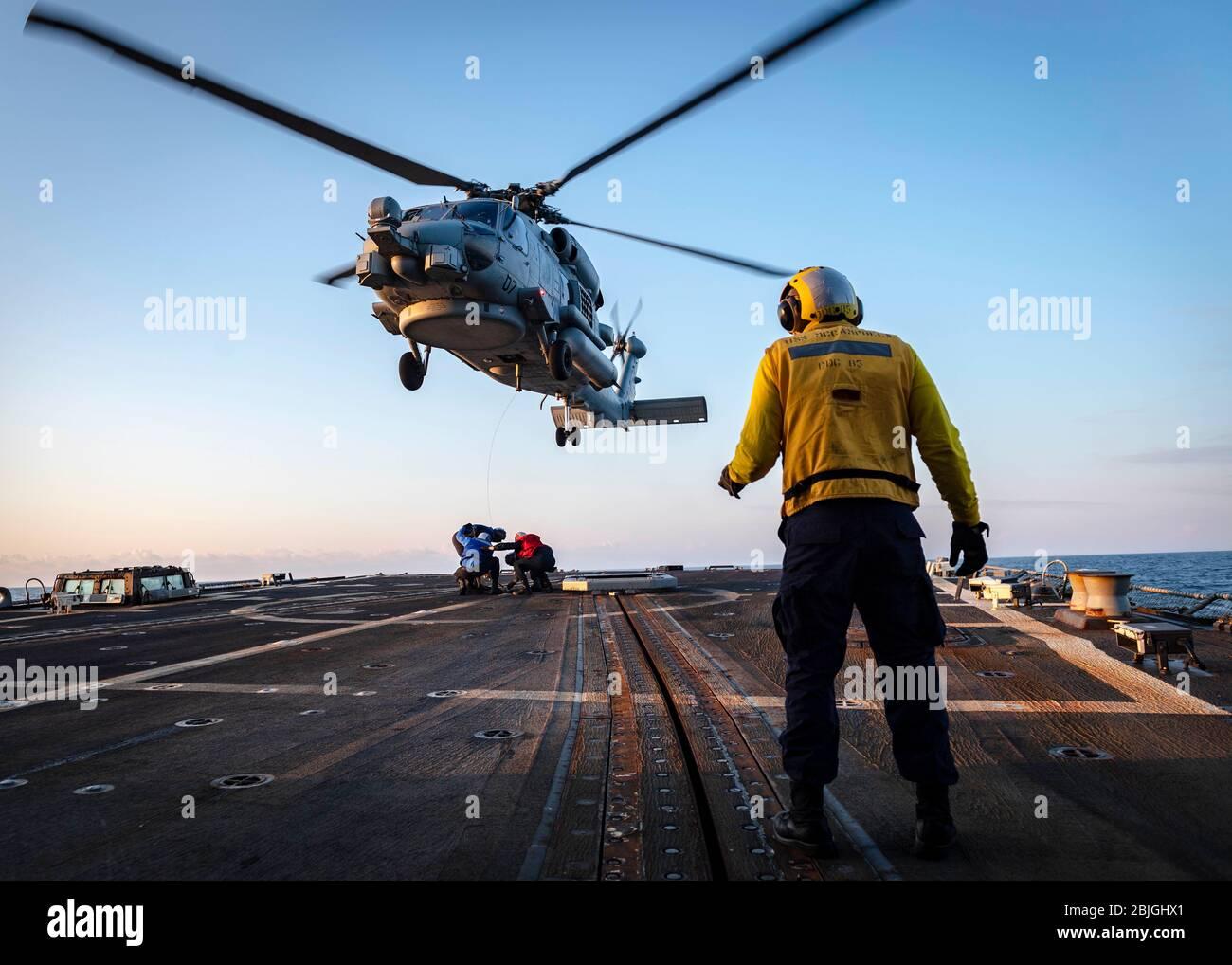 """200427-N-WI365-2055 MAR DE JAPÓN (ABRIL 27, 2020) – los marineros estadounidenses simulan una asistencia de recuperación con un helicóptero MH-60 sea Hawk, asignado a los """"señores de la guerra"""" del escuadrón de la huelga Marítima del helicóptero (HSM) 51, en la cubierta de vuelo a bordo del destructor de misiles guiados USS McCampbell (DDG 85) de la clase Arleigh Burke. McCampbell está realizando operaciones en la región del Indo-Pacífico mientras que está asignado al Escuadrón Destroyer (DESRON) 15, el mayor DESRON desplegado hacia adelante de la Marina y la principal fuerza de superficie de la 7a flota de los Estados Unidos. (EE.UU Foto de la Marina por Especialista en Comunicación de masas de segunda clase Markus Castañeda) Foto de stock"""