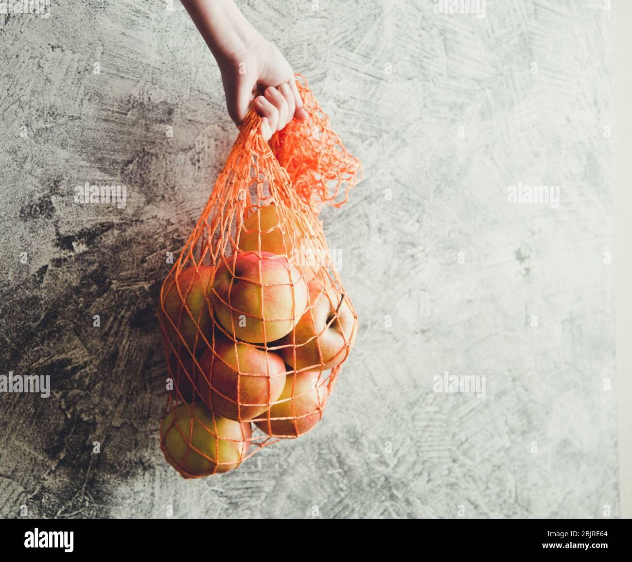 Concepto-ecología, conservación de la naturaleza, sin bolsas de plástico. Bolsa de malla reutilizable con manzanas, espacio de copia/ Foto de stock