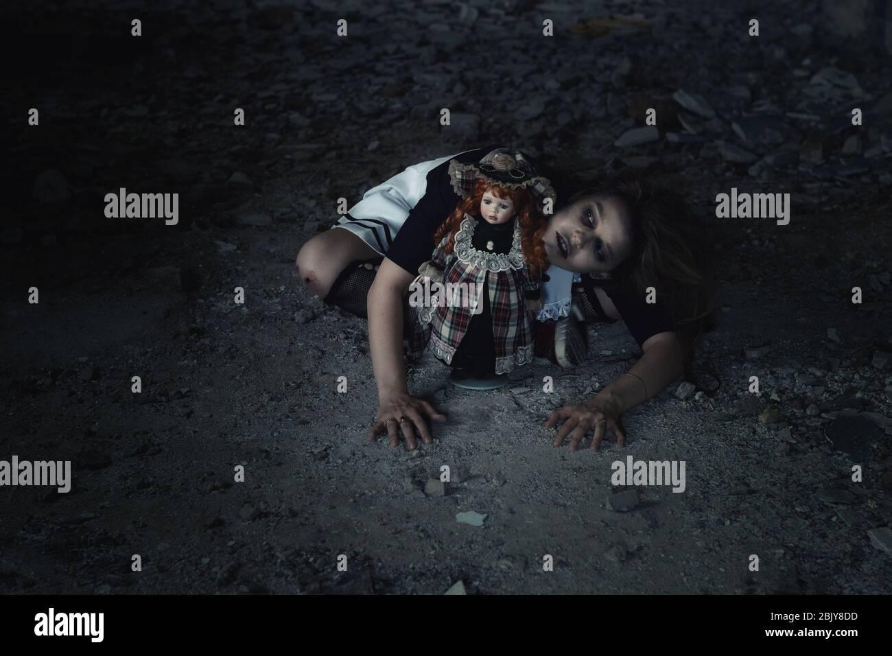 niña asustadiza con una muñeca en una casa abandonada Foto de stock