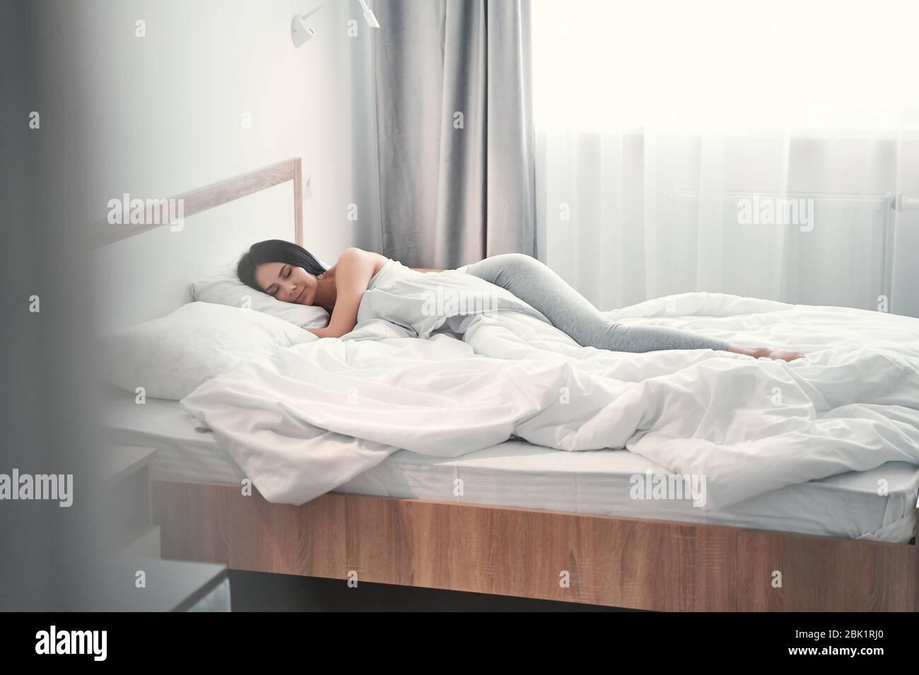 Mujer joven relajada que se aloja en casa sola Foto de stock