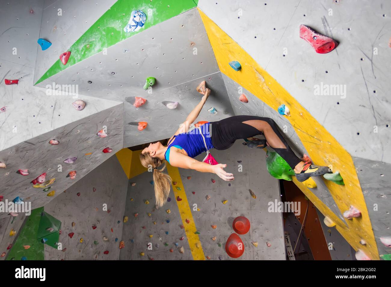 Mujer escaladora colgando en una pared de escalada, dentro de ganchos de colores. Foto de stock
