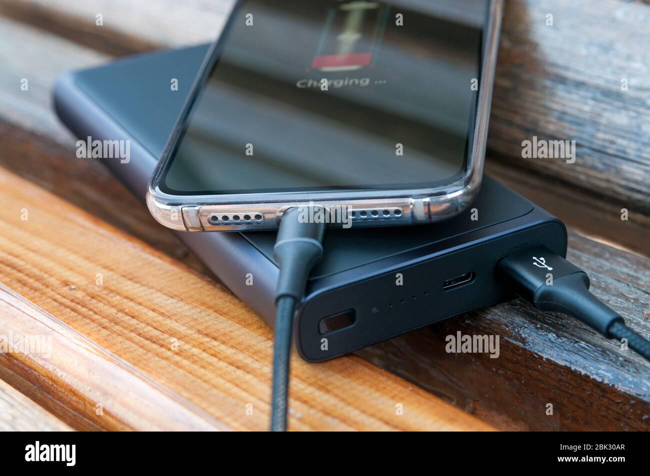 El smartphone moderno se carga desde la fuente de alimentación sobre el fondo de madera. Concepto de tecnología moderna. Enfoque selectivo. Foto de stock