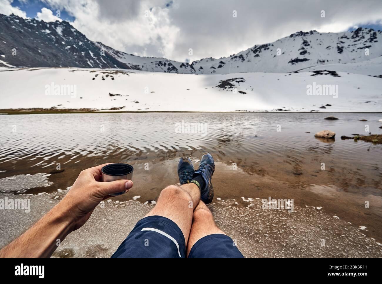 Taza de Té y las piernas del hombre en zapatos de Seguimiento y vista sobre el lago glaciar cubierto de nieve en las montañas Foto de stock