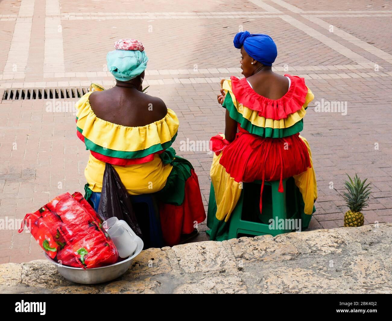 Cartagena, Colombia, 1 de agosto de 2019: Dos palenqueras vendedores callejeros de frutas típicas con vestidos de colores sentados descansando desde la espalda Foto de stock