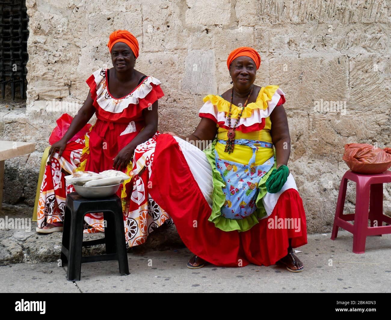 Cartagena, Colombia, 1 de agosto de 2019: Dos palenqueras vendedores callejeros de frutas típicas con vestidos de colores sentados descansando desde el frente Foto de stock