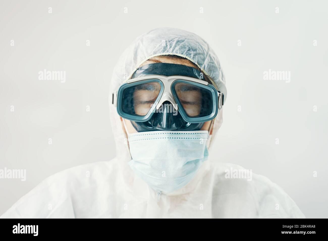 Médico muy cansado con los ojos cerrados. Hombre profesional en traje con capucha para protección contra riesgos biológicos Foto de stock