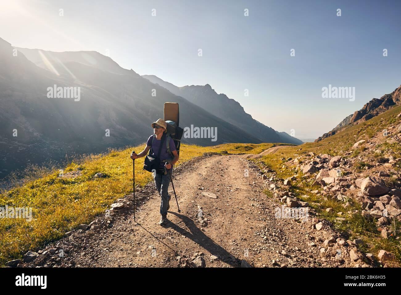 Excursionista con mochila grande es caminando por la carretera con espectaculares montañas en segundo plano Foto de stock