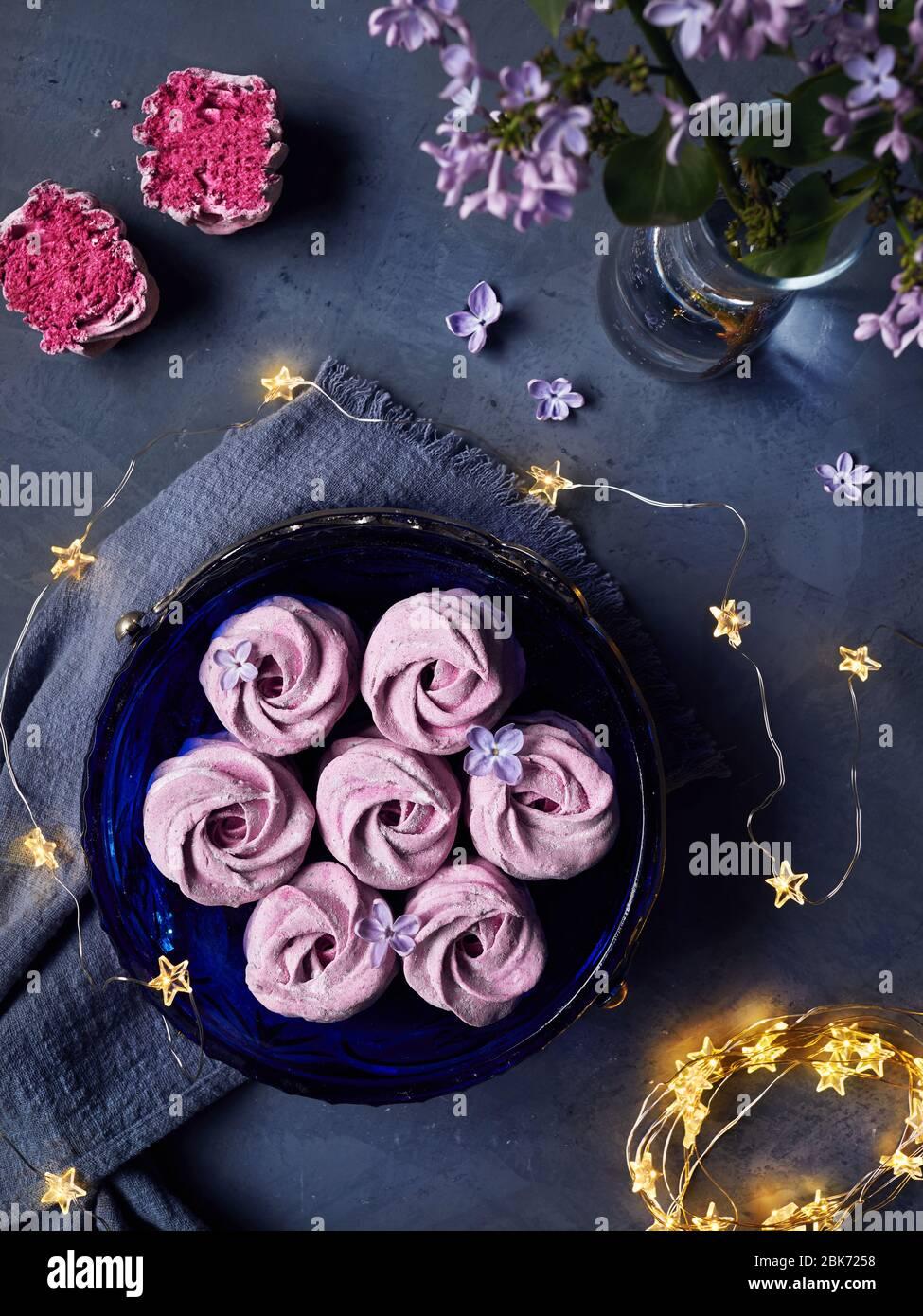 Zephyr o Marshmallow caseros dulces violeta atmosférico de grosella negra cerca de flores lilas y estrellas mágicas luces en la vista superior de fondo oscuro Foto de stock