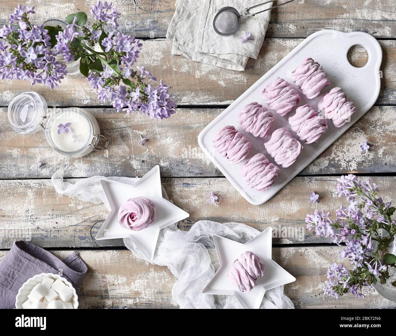 Violeta dulce casero Zephyr o Marshmallow de grosella negra cerca de las flores lilas en la mesa de madera vista en colores pastel violeta Foto de stock