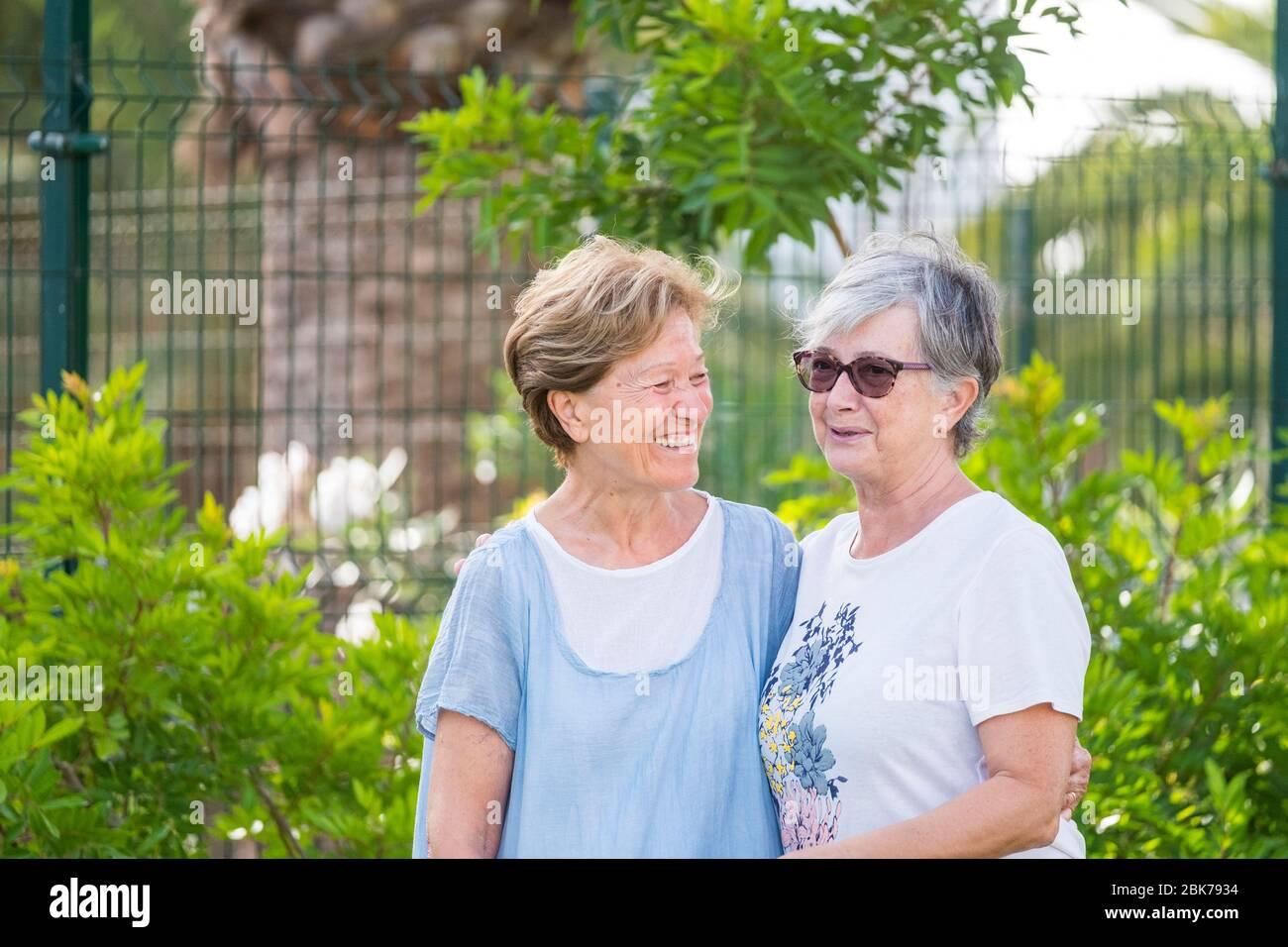 Pareja mayor mujeres caucásicas amigos se divierten y disfrutan de contacto social y amistad al aire libre después de la sujeción para coronavirus y son felices para el healt Foto de stock