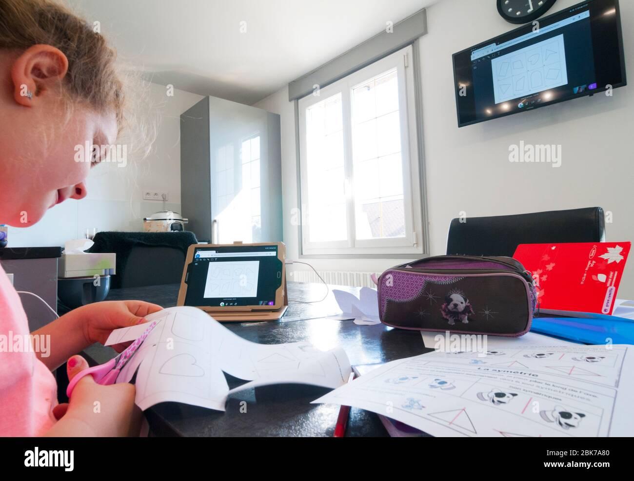 Francia, Loiret (45), Covid-19 cierre francés el 04/27/2020, niña de 7 años en CE1 durante la clase virtual de la escuela en casa utilizando la tableta remota Foto de stock