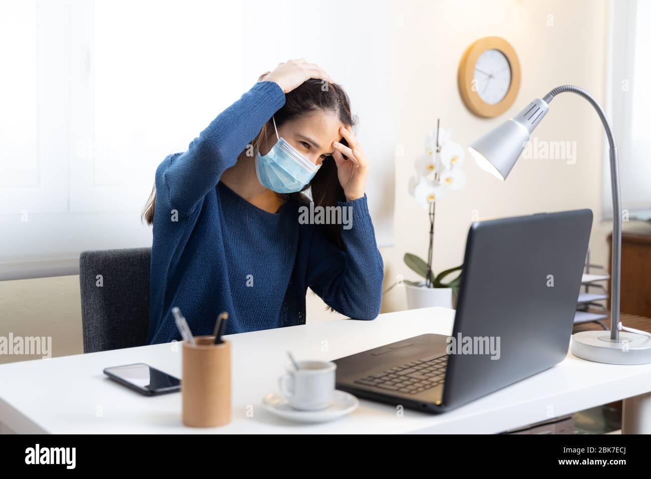Un estudiante adolescente con máscara facial se queja de dolor de cabeza con la computadora en casa Foto de stock