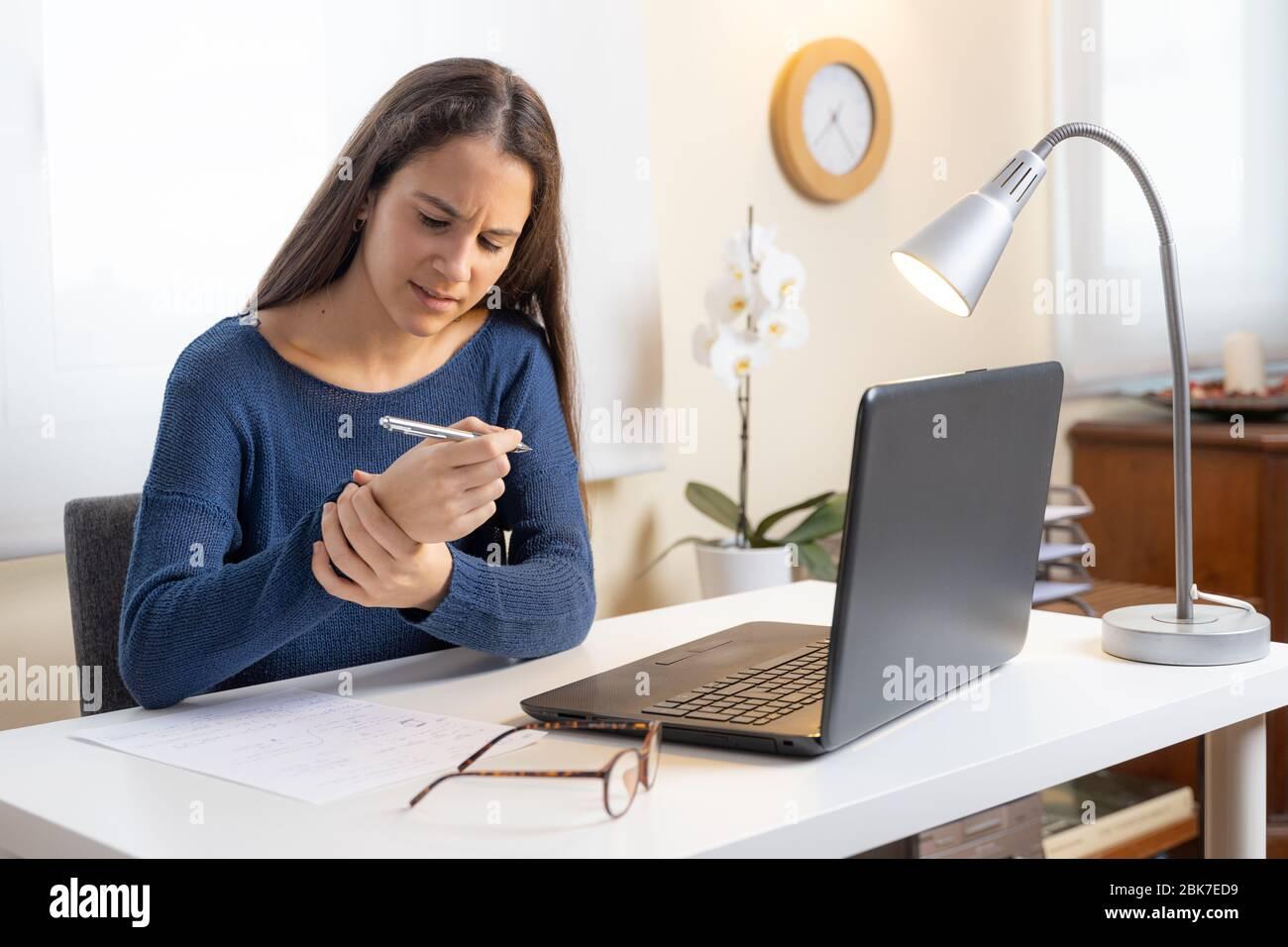 Niña adolescente con computadora en casa quejándose de dolor en la muñeca Foto de stock