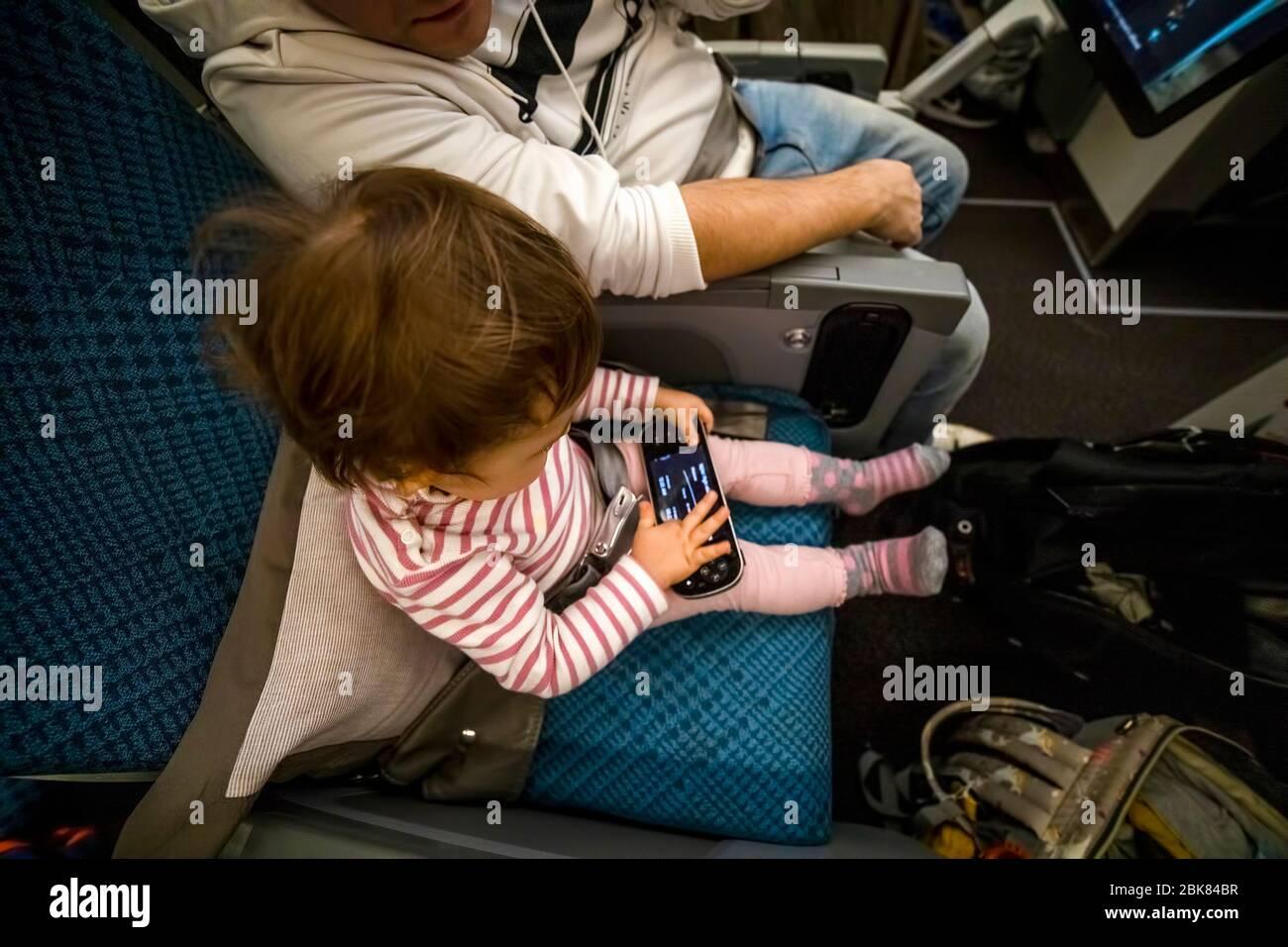 entretenimiento a bordo del avión en vuelo. bebé sentado en el avión en el asiento y jugar divertido en el sistema multimedia remoto. Foto de stock
