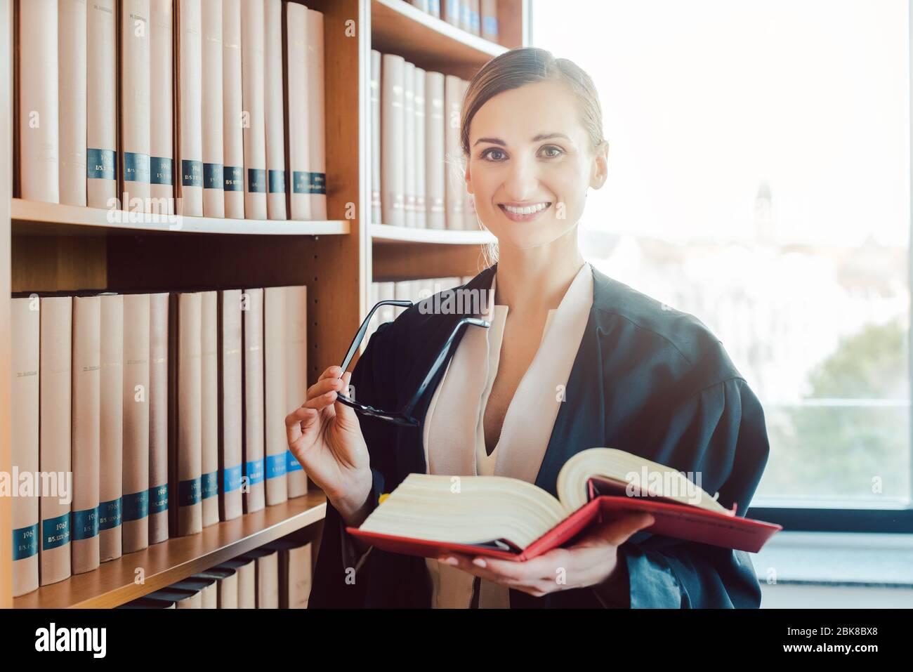 Abogado trabajando en un caso difícil de leer en la biblioteca Foto de stock