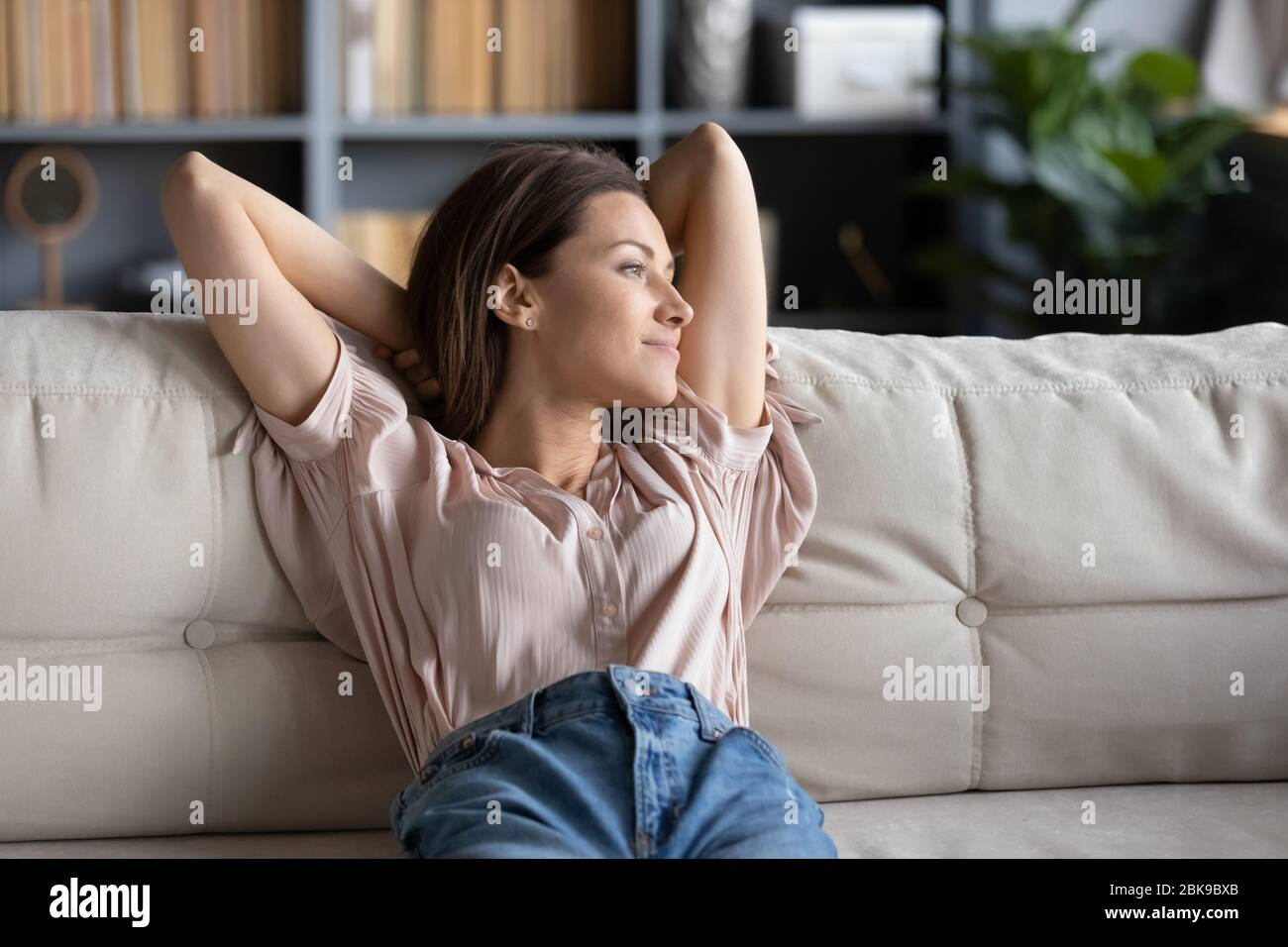 Mujer joven tranquila relajándose en el sofá en casa Foto de stock