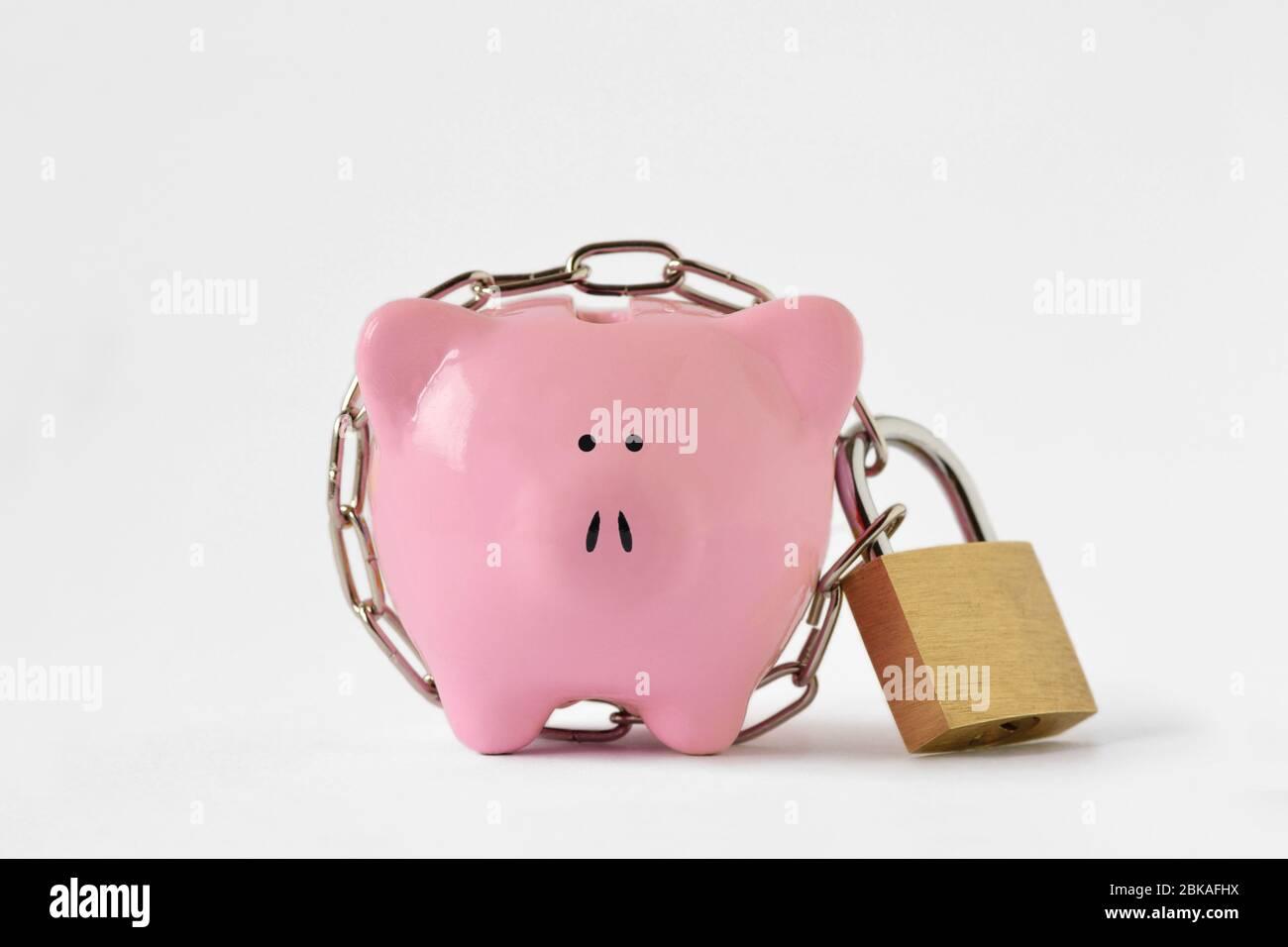 Banco piggy cerrado con cadena y candado sobre fondo blanco - concepto de ahorro y protección financiera Foto de stock