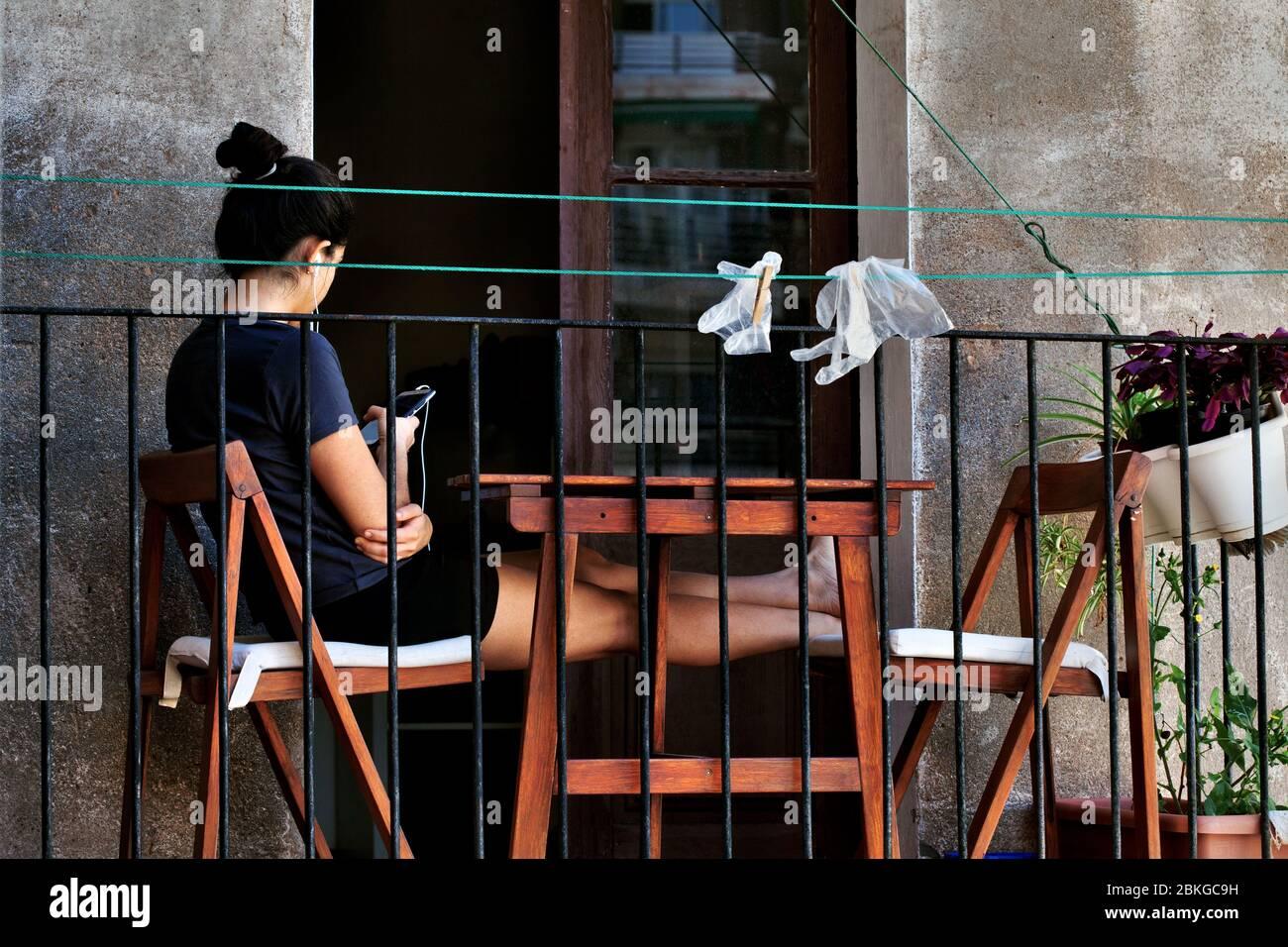La joven se sentó en su balcón usando su smartphone. Foto de stock